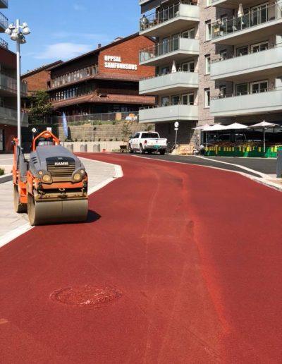 asfaltering med rød asfalt på gangvei i boligområde